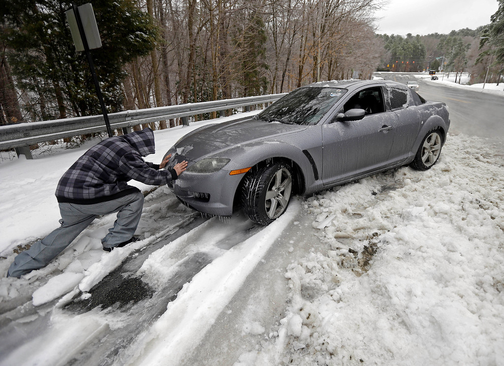 . Passerby Leo Cruz helps push a car from the frozen roadside in Chapel Hill, N.C., Thursday, Feb. 13, 2014. The owner abandoned the car overnight during the storm. The National Weather Service issued a winter storm warning lasting into Thursday covering 95 of the state\'s 100 counties. (AP Photo/Gerry Broome)
