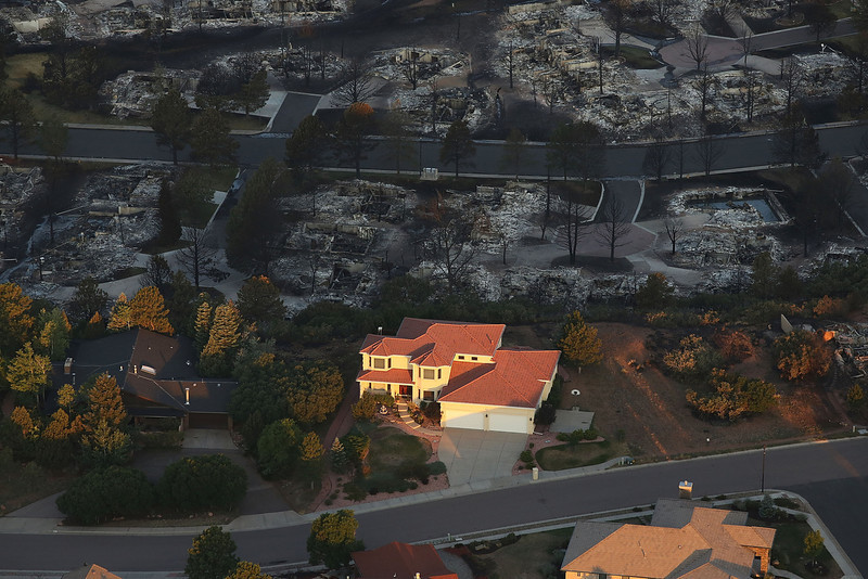 . Destroyed homes sit beside a home left untouched by fire in a neighborhood affected by the Waldo Canyon fire on June 30, 2012 in Colorado Springs, Colorado. The massive fire, which has eased with the help of cooler temperatures and lighter winds, has destroyed hundreds of homes and forced more than 35,000 people to flee. The fire was estimated at 17,073 acres and was 25 precent contained with some evacuees being let back into their neighborhoods. A second body has been located in a burned home while others are still reported missing.  (Photo by Spencer Platt/Getty Images)