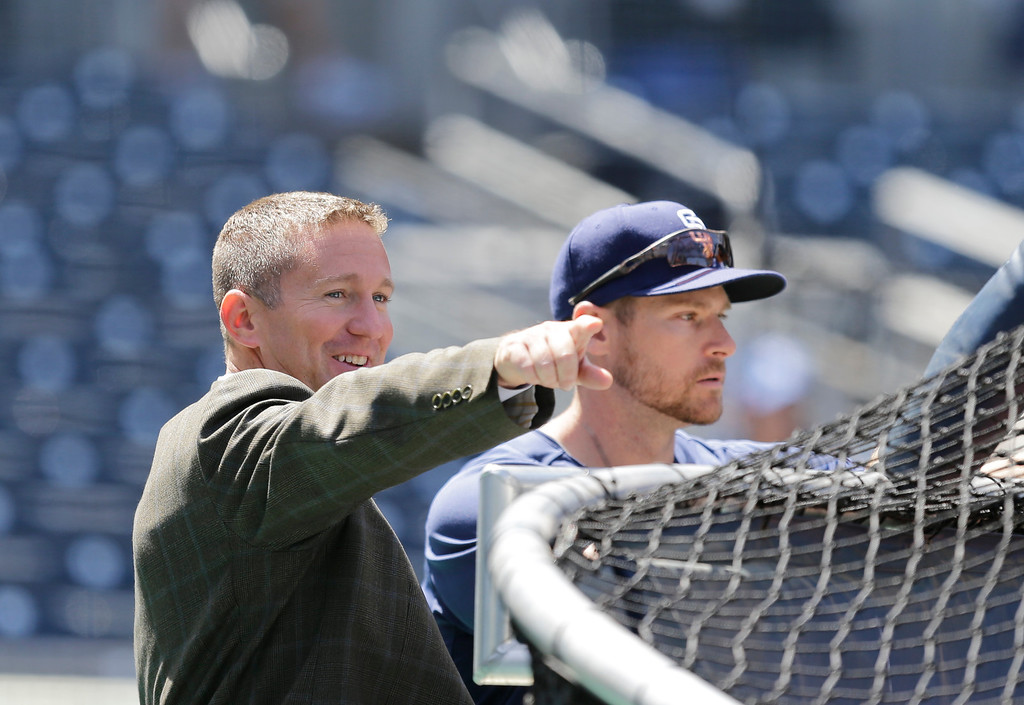 . San Diego Padres general manager Josh Byrnes talks with injured third baseman Chase Headley during warm ups before the home opener against the Los Angeles Dodgers in San Diego, Tuesday, April 9, 2013. (AP Photo/Lenny Ignelzi)