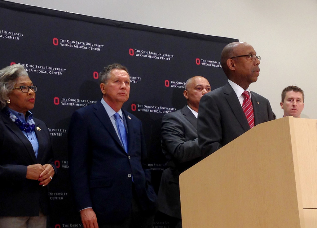 . Ohio Gov. John Kasich, second from left, listens as Ohio State University President Michael Drake speaks during a news conference Monday, Nov. 28, 2016, in Columbus, Ohio. A Somali-born Ohio State University student plowed his car into a group of pedestrians on campus and then got out and began stabbing people with a knife Monday before he was shot to death by an officer. (AP Photo/Juile Smyth)