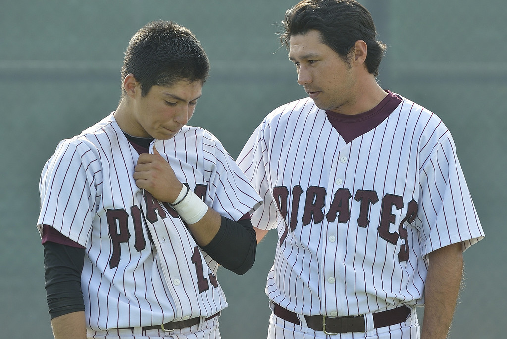 . PARAMOUNT, CALIF. USA -- Paramount coach Andrew Yonaki, right, console Frankie Valenzuela (15) after their CIF-SS Division III playoff loss to Westminster in Paramount, Calif., on Thursday, May 16, 2013. Westminster defeated Paramount, 3 to 0.  Photo by Jeff Gritchen / Los Angeles Newspaper Group
