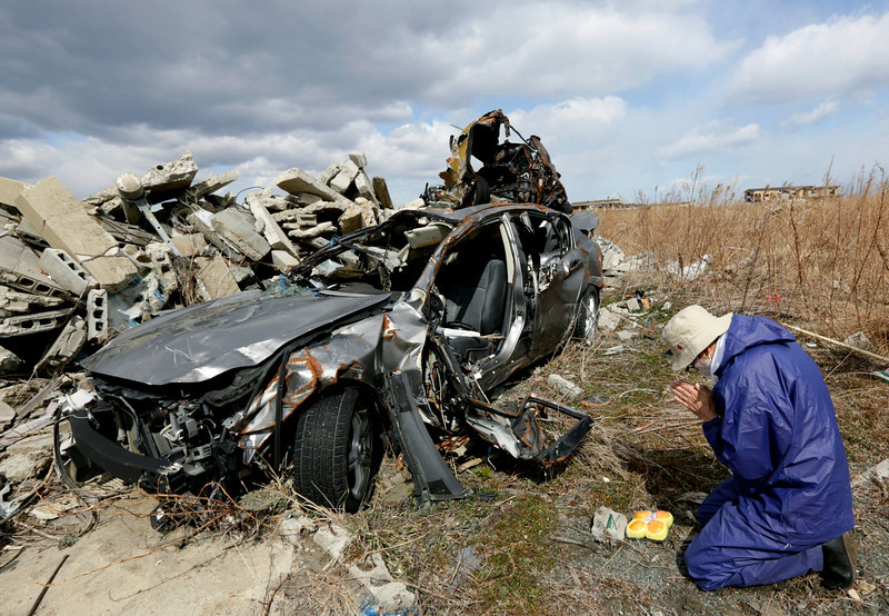 . Koichi Yamada offers a prayer for his friend Kenichi Sato killed by tsunami at his friend\'s destroyed car in the tsunami-devastated Ukedo area in entry-restricted town of Namie, Fukushima Prefecture, northern Japan, five kilometers north of Tokyo Electric Power Co.\'s Fukushima Daiichi Nuclear Power Plant, 11 March 2014. A 9.0 magnitude earthquake on 11 March 2011 struck off the coast of Japan followed by a tsunami that triggered the nation\'s worst nuclear accident at Fukushima Daiichi Nuclear Power Plant in nearby Fukushima. The disaster left about 19,000 people dead and missing.  (EPA/KIMIMASA MAYAMA)