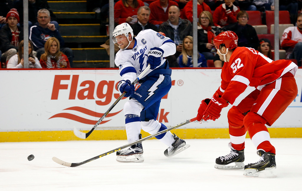 . Tampa Bay Lightning center Steven Stamkos (91) shoots as Detroit Red Wings defenseman Jonathan Ericsson (52) defends in the first period of an NHL hockey game Saturday, March 28, 2015, in Detroit. (AP Photo/Paul Sancya)
