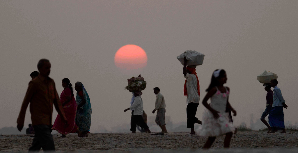 . Hindu devotees walk back from the River Ganges after performing rituals during sunset on Chhath Puja festival in Patna, India, Friday, Nov. 8, 2013. (AP Photo/Aftab Alam Siddiqui)