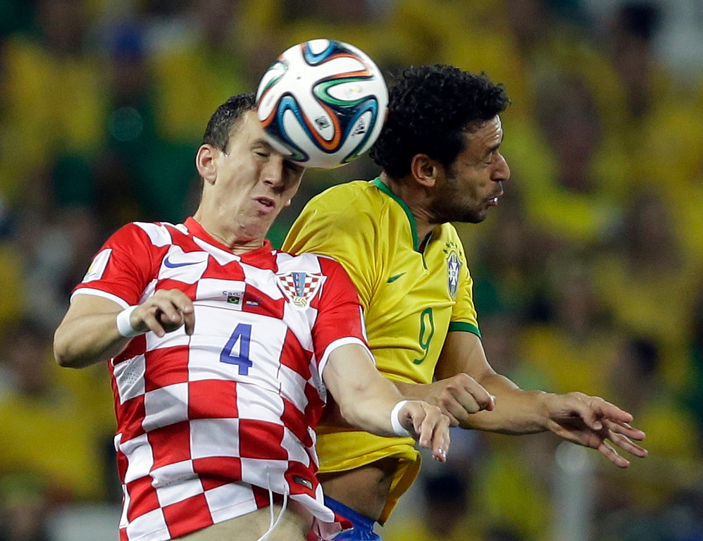 . Croatia\'s Ivan Perisic, left, wins a header from Brazil\'s Fred during the group A World Cup soccer match between Brazil and Croatia, the opening game of the tournament, in the Itaquerao Stadium in Sao Paulo, Brazil, Thursday, June 12, 2014. (AP Photo/Kirsty Wigglesworth)