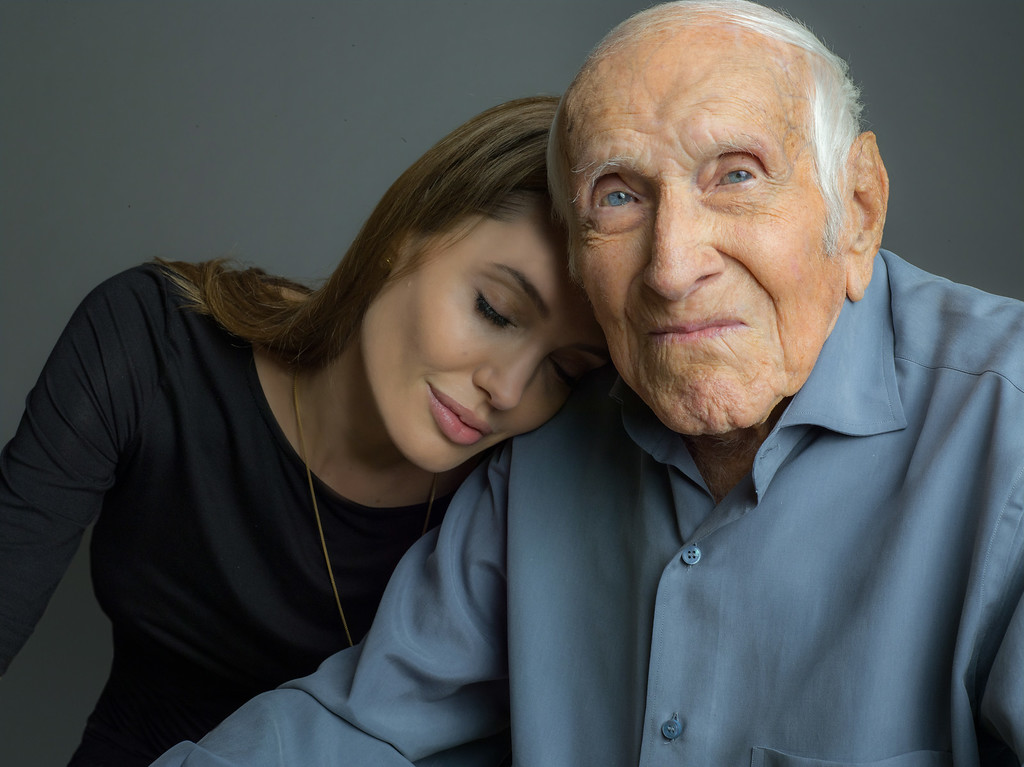". This undated photo provided by Universal Pictures, Angelina Jolie is photographed with Louis Zamperini. Zamperini, a U.S. Olympic distance runner and World War II veteran who survived 47 days on a raft in the Pacific after his bomber crashed, then endured two years in Japanese prison camps, died Wednesday, July 2, 2014, according to Universal Pictures studio spokesman Michael Moses. He was 97.  Jolie is directing the Universal movie, ""Unbroken,\"" about the life of Zamperini. (AP Photo/Universal Pictures)"