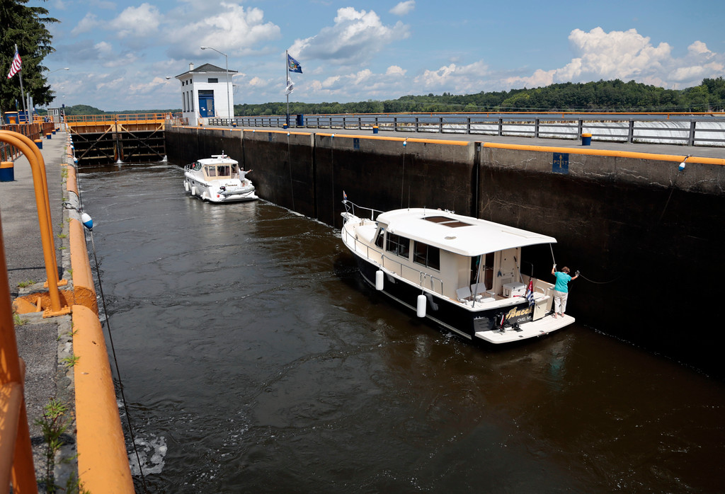 . In this Tuesday, Aug. 4, 2015 photo, boats wait for Lock 7 on the Erie Canal to fill before continuing their journey in Niskayuna, N.Y. The Erie Canal was an engineering marvel when it opened in 1825, linking the Hudson River to the Great Lakes and humming with activity that opened up the West. Now a renewed court fight has drawn fresh attention to the 360-mile-long ribbon of channels, lifts and locks between Albany and Buffalo, calling into question whether taxpayers will again have to foot the hefty bill to keep it and the other canals in the system operating.  (AP Photo/Mike Groll)