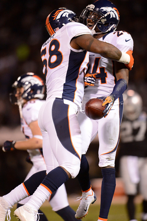 . Denver Broncos cornerback Champ Bailey (24) celebrates his interception with Denver Broncos outside linebacker Von Miller (58) on a pass  intended for Oakland Raiders tight end Brandon Myers (83) during the first quarter Thursday, December 6, 2012 during Thursday Night Football at O.c Coliseum in Oakland  John Leyba, The Denver Post