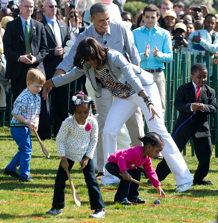 . US President Barack Obama (C) and First Lady Michelle Obama cheer on children as they race to roll eggs as they participate in the White House Easter Egg Roll on the South Lawn of the White House in Washington, DC, April 1, 2013. Obama hosts the annual event, featuring live music, sports courts, cooking stations, storytelling and Easter egg rolling. AFP PHOTO / Saul LOEB/AFP/Getty Images