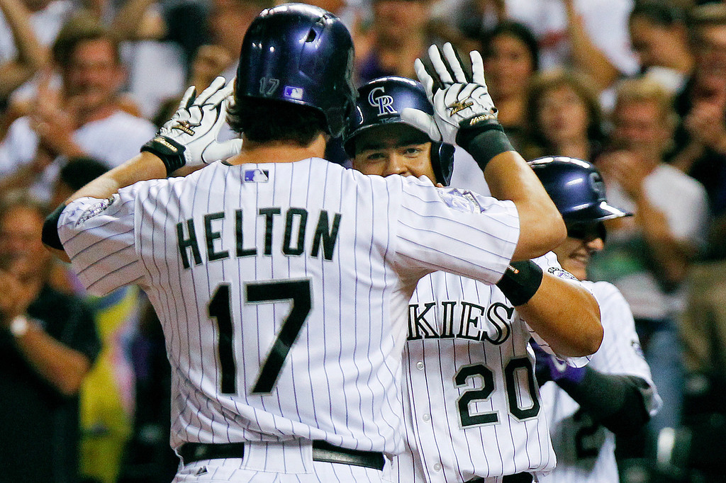 . Colorado Rockies\' Todd Helton (17) is congratulated by Wilin Rosario (20) after hitting his second three-run home run of the night during the seventh inning of a baseball game against the Cincinnati Reds, Friday, Aug. 30, 2013, in Denver. (AP Photo/Barry Gutierrez)