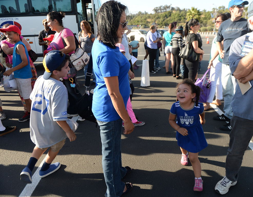 . 2 1/2 year-old Giuliana, right, runs around her mother Nancy as members of the San Fernando Valley Rescue Mission are treated to a Major league baseball game between the Miami Marlins and the Los Angeles Dodgers on Wednesday, May 14, 2014 in Los Angeles. The Mission experienced a devastating fire earlier this month. Damage sustained included the destruction of the San Fernando Valley Rescue Mission�s emergency shelter, vehicle fleet, clothing warehouse and food pantry which were vital in aiding those of need in the San Fernando Valley.  (Keith Birmingham/Pasadena Star-News)