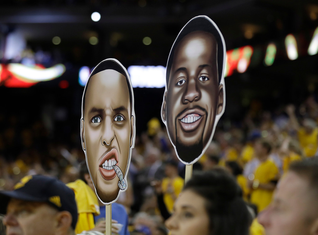 . A fan holds up signs of Golden State Warriors guard Stephen Curry and forward Draymond Green during the second half of Game 2 of basketball\'s NBA Finals between the Golden State Warriors and the Cleveland Cavaliers in Oakland, Calif., Sunday, June 4, 2017. (AP Photo/Marcio Jose Sanchez)