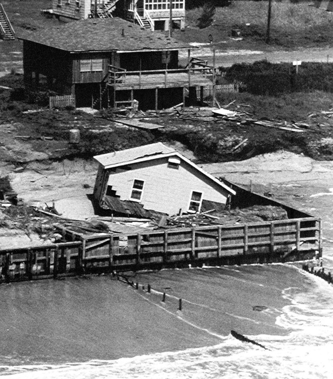 . A home at Holden Beach, North Carolina lost some of its roof and siding after being knocked of its foundation when Hurricane Hugo struck the Carolina coast on Friday, Sept. 23, 1989 Holden Beach, North Carolina. Other homes close by escaped with little visible damage. (AP Photo/Bob Bridges)