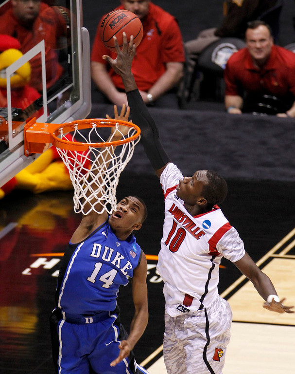 . Louisville Cardinals center Gorgui Dieng (10) blocks a shot by Duke Blue Devils guard Rasheed Sulaimon (14) in the first half during their Midwest Regional NCAA men\'s basketball game in Indianapolis, Indiana, March 31, 2013. REUTERS/John Sommers II