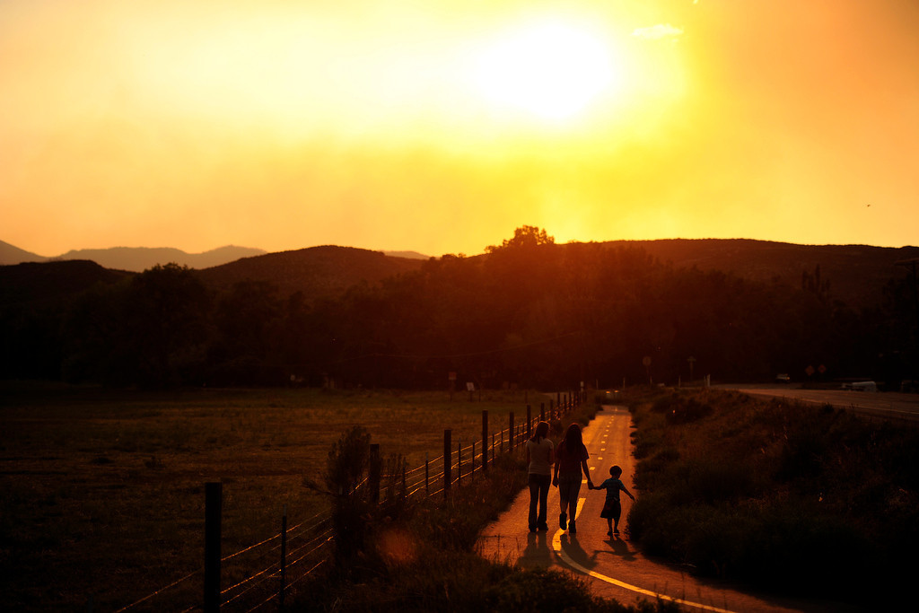 . Samantha Hunt holds hands with Dominic (no last name provided) while walking with Tasha Snider at sundown as the High Park Fire burns west of Laporte on Monday, June18, 2012. AAron Ontiveroz, The Denver Post