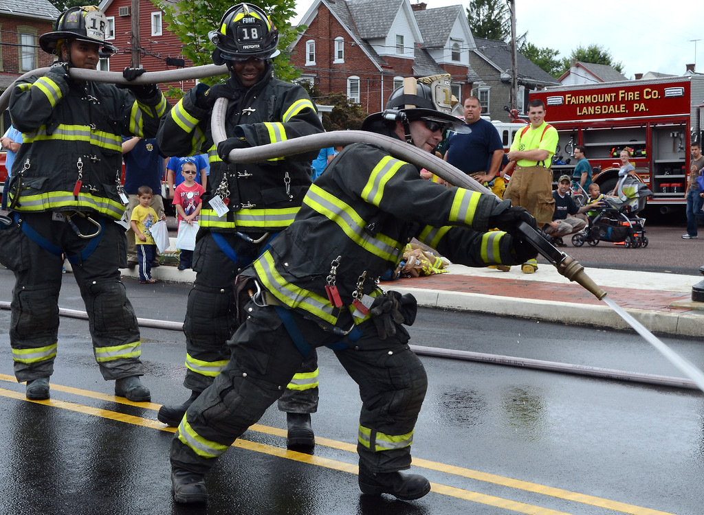 . Fairmount Fire Company members participate in a water battle demonstration for the Fairmount Fire Company 125th Anniversary festivities during the Lansdale Founders Day celebration on Saturday August 23,2014. Photo by Mark C Psoras/The Reporter