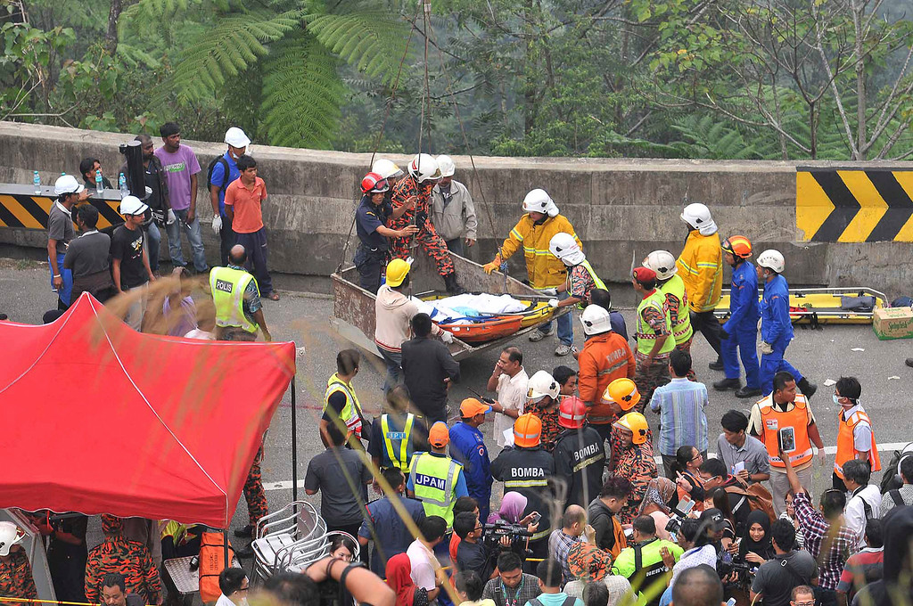. Malaysian emergency services personnel rescue a passenger by a crane after a passenger bus carrying tourists and local residents fell into a ravine near the Genting Highlands, about an hour\'s drive from Kuala Lumpur, Malaysia, Wednesday, Aug. 21, 2013.  (AP Photo) MALAYSIA OUT