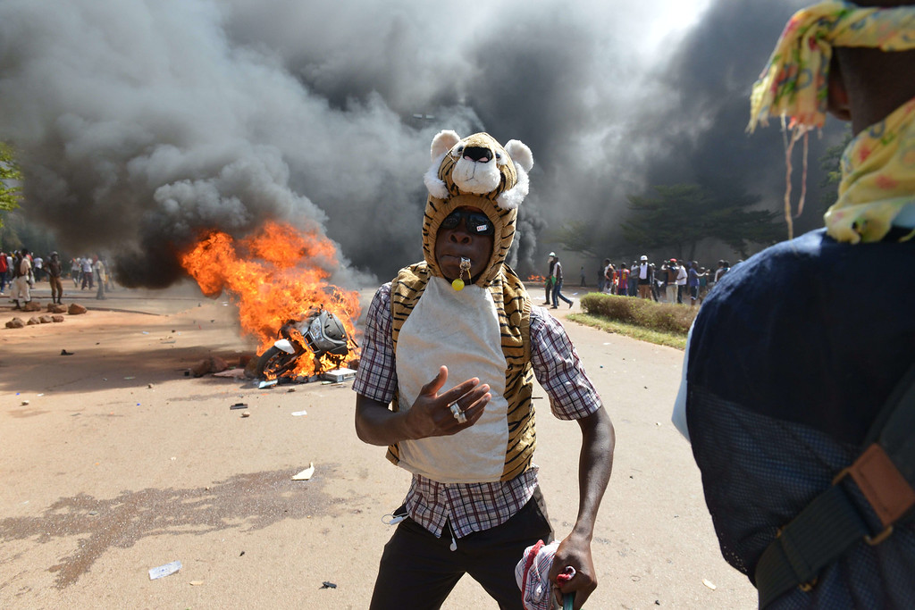 . A protester stands outside the parliament in Ouagadougou on October 30, 2014 as cars and documents burn outside. Hundreds of angry demonstrators in Burkina Faso stormed parliament on October 30 before setting it on fire in protest at plans to change the constitution to allow President Blaise Compaore to extend his 27-year rule. Police had fired tear gas on protesters to try to prevent them from moving in on the National Assembly building ahead of a vote on the controversial legislation. But about 1,500 people managed to break through the security cordon and were ransacking parliament.  SSOUF SANOGO/AFP/Getty Images