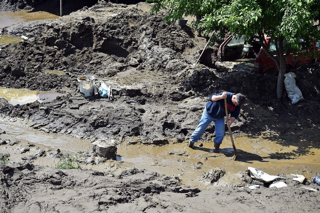 . A man clears mud from his front yard in  Krupanj, some 130 kilometers south west of Belgrade, on May 20, 2014, after it was hit with floods and landslides, cutting the western Serbian town off for four days. Serbia declared three days of national mourning on May 20 as the death toll from the worst flood to hit the Balkans in living memory rose and health officials warned of a possible epidemic. At least 49 people have been killed already by the worst floods in central Europe for a century and more than 1.6 million people have been hit as the river Sava and its tributaries have burst their banks, inundating tens of thousands of hectares of farmland and destroying houses and buildings.   AFP PHOTO / ANDREJ ISAKOVIC/AFP/Getty Images