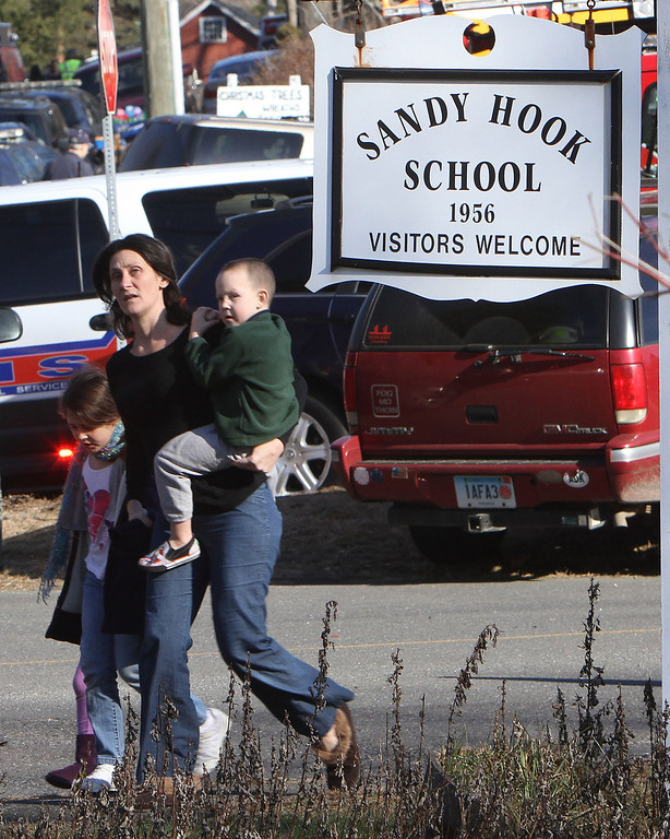 . A parent walks away from the Sandy Hook Elementary School with her children following a shooting at the school in Newtown, Conn. on Friday, Dec. 14, 2012. (AP Photo/The Journal News, Frank Becerra Jr.)