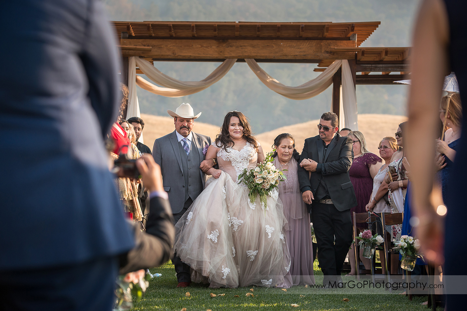 bride walking down the aisle with parents during wedding ceremony at Taber Ranch Vineyards