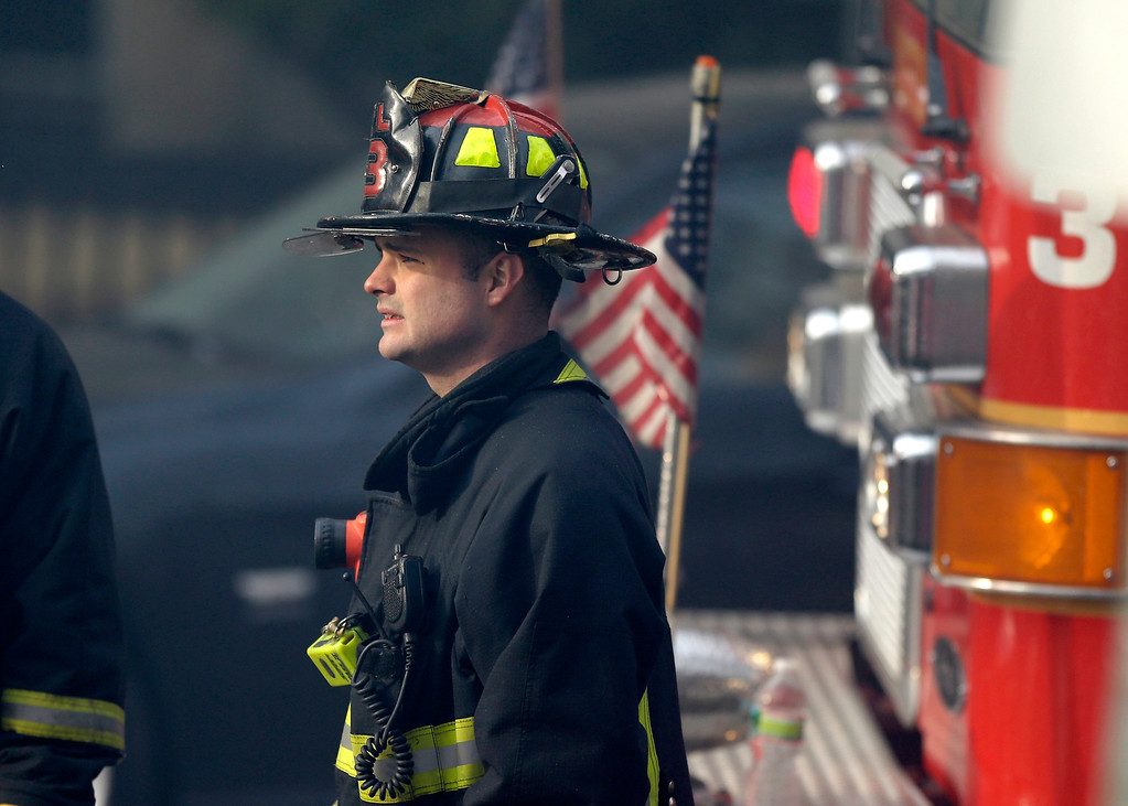 . A firefighter looks on at the scene of a multi-alarm fire at a four-story brownstone in the Back Bay neighborhood near the Charles River, Wednesday, March 26, 2014, in Boston.  (AP Photo/Steven Senne)