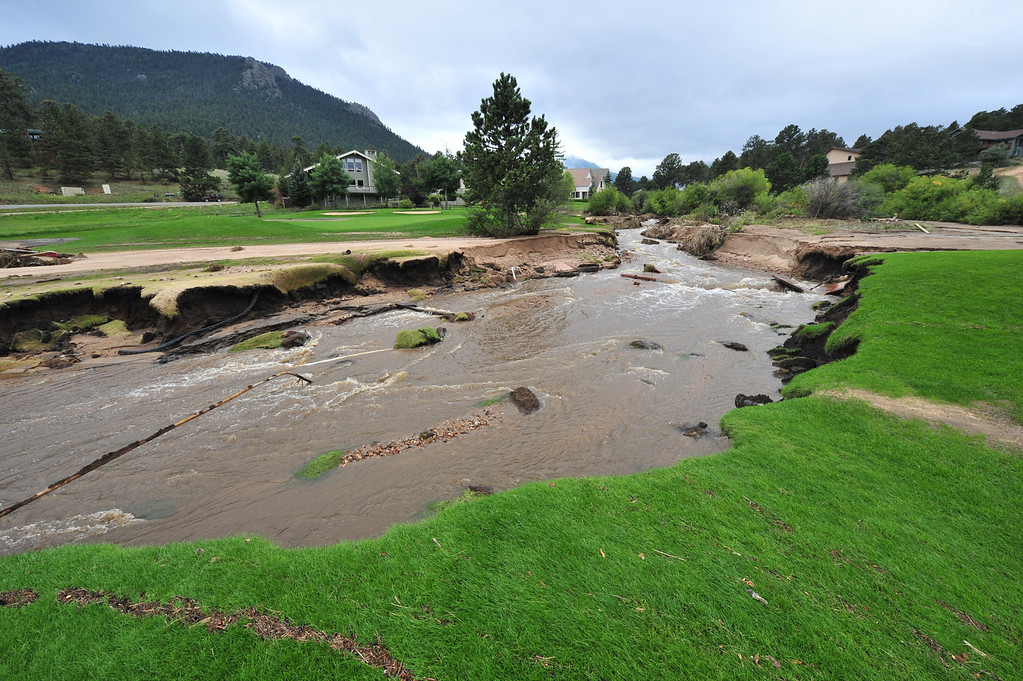 . The 17th green sits cut off from the fairway at the Estes Park Public 18-Hole Golf Course on Thursday, Sept. 19, 2013. Last week\'s flood tore away bridges and land on the course close to the Fish Creek.   Walt Hester/Estes Park Trail-Gazette