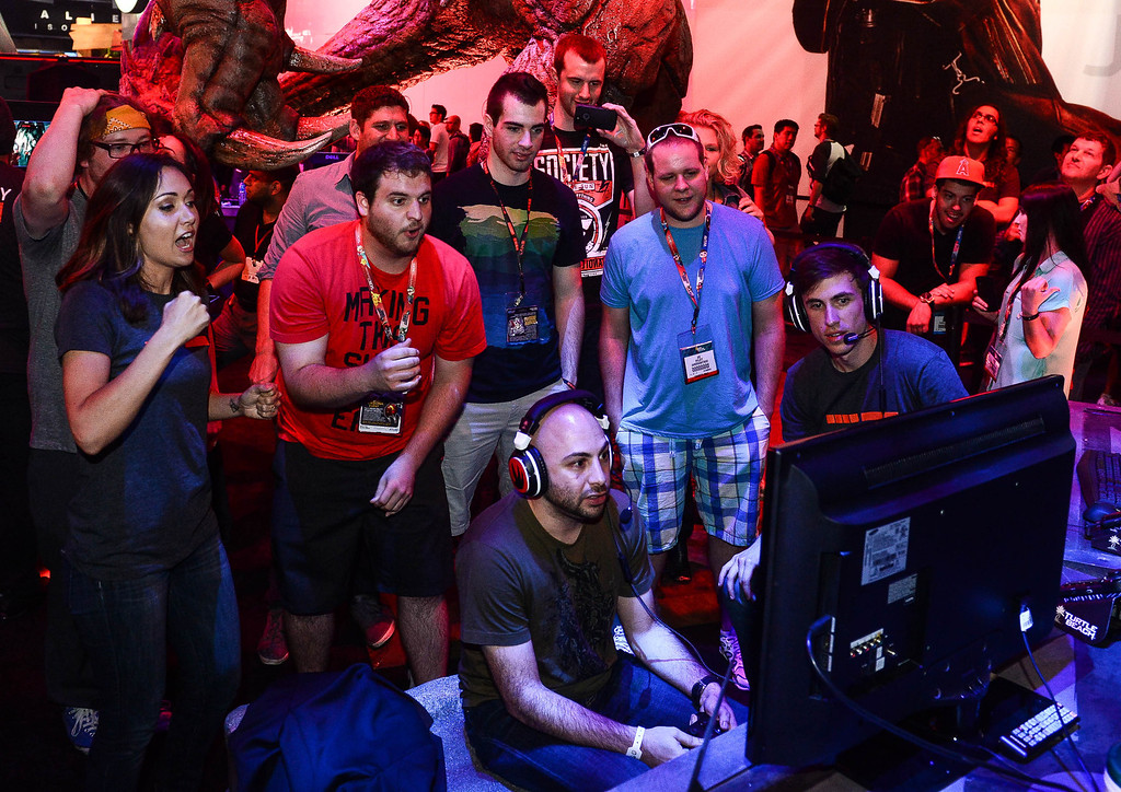 ". Gamers react as they play the video game ""Evolve\"" at Electronic Entertainment Expo in Los Angeles on Tuesday, June 10, 2014. (Photo by Watchara Phomicinda)"