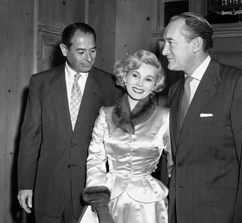 . Host  Jerome Ohrbach greets Zsa Zsa Gabor and her husband George Sanders on Dec. 12, 1952 in Los Angeles.     (AP Photo/Eddie Widdis)