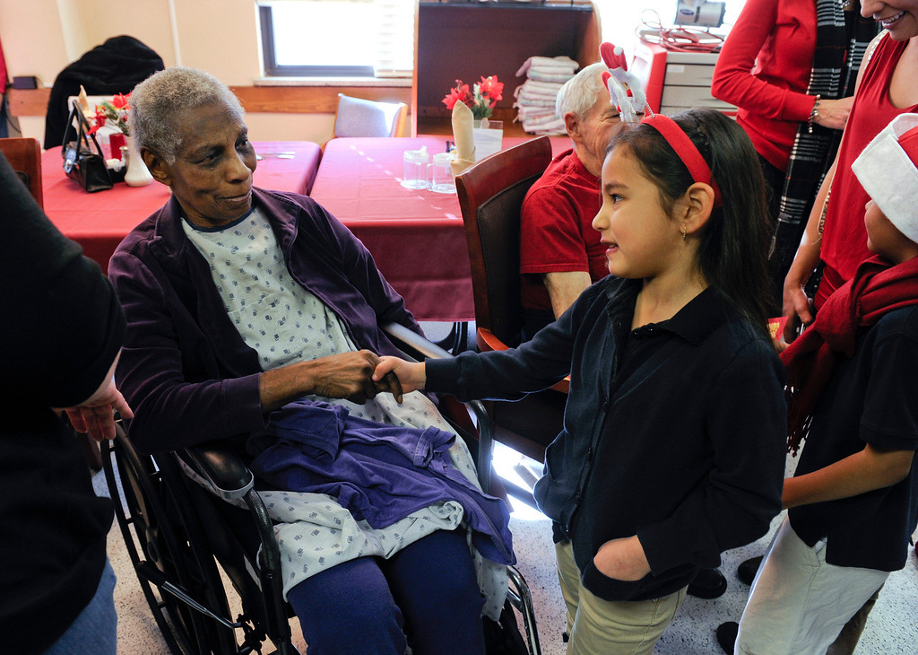 . Mae Ward, left, is greeted by Dayanna Sarmiento, 5, after the students and parents from the Denver Center for International Studies at Ford Elementary School spend a Saturday singing holiday songs in three different languages to the residents of the Kindred Care nursing home. (Photo by Kathryn Scott Osler/The Denver Post)
