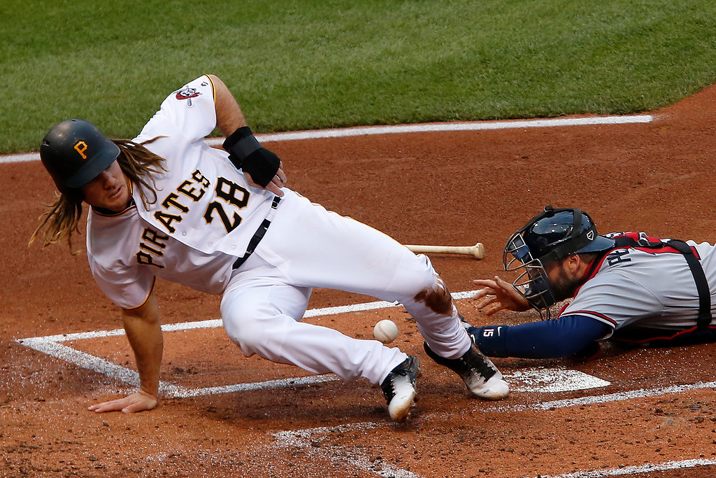 . Pittsburgh Pirates\' John Jaso (28) knocks the ball out of the glove of Atlanta Braves catcher A.J. Pierzynski to score on a ball hit by Jung Ho Kang during the first inning of a baseball game in Pittsburgh, Tuesday, May 17, 2016. (AP Photo/Gene J. Puskar)