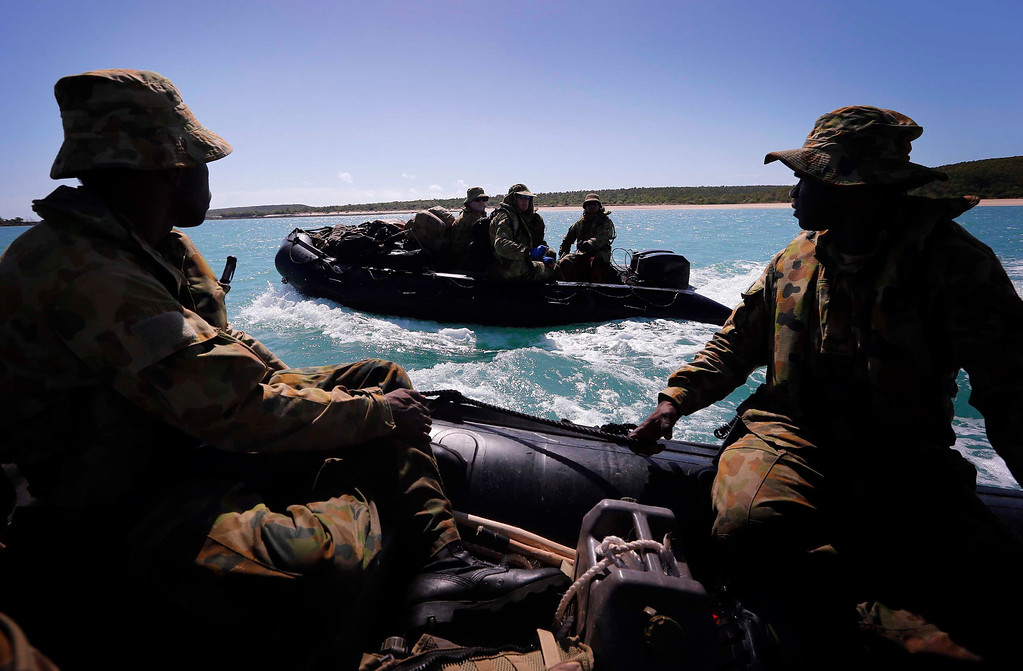 . Soldiers from Australia\'s North West Mobile Force (NORFORCE) unit patrol in inflatable boats, along the coastline of Cotton Island, part of the English Company Islands, located inside Arnhem Land in the Northern Territory July 17, 2013. NORFORCE is a surveillance unit that employs ancient Aboriginal skills to help in the seemingly impossible task of patrolling the country\'s vast northwest coast. NORFORCE\'s area of operations is about 1.8 million square km (700,000 square miles), covering the Northern Territory and the north of Western Australia. Aboriginal reservists make up a large proportion of the 600-strong unit, and bring to bear their knowledge of the land and the food it can provide. Fish, shellfish, turtle eggs and even insects supplement rations during the patrol, which is on the lookout for illegal foreign fishing vessels and drug smugglers, as well as people smugglers from  neighboring Indonesia. Picture taken July 17, 2013. REUTERS/David Gray