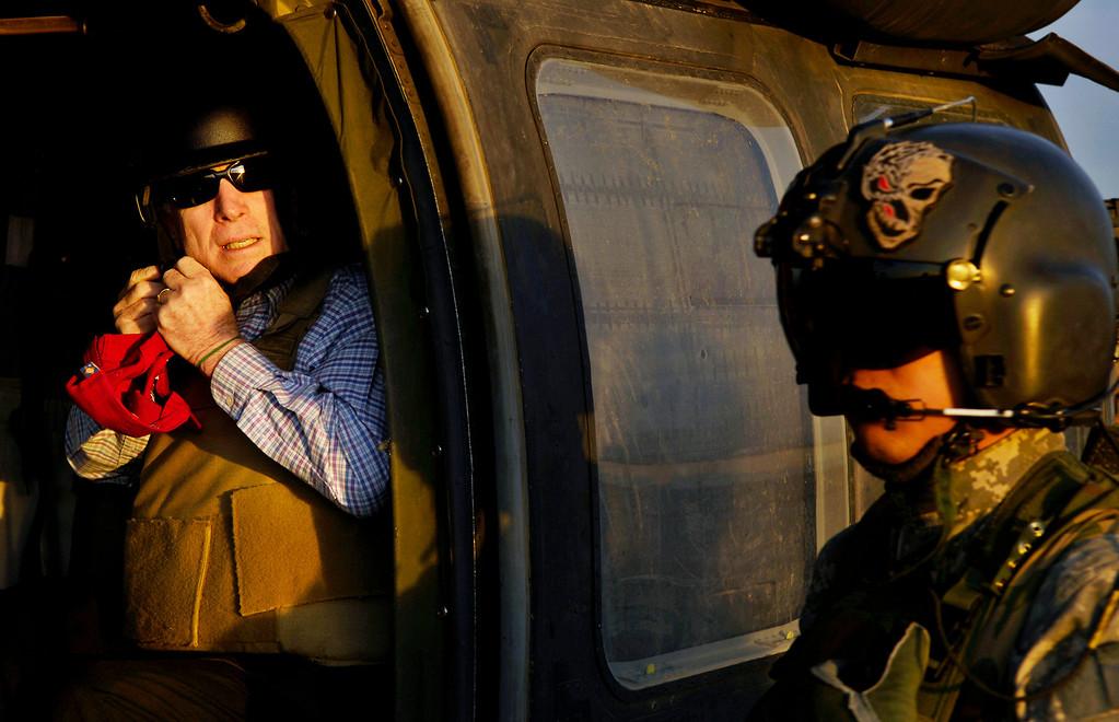 . US Republican presidential candidate Senator John McCain (R-AZ) unbuckles his flight helmet as he arrives at Sather Air Base in Baghdad, March 16, 2008. Picture taken March 16, 2008.  REUTERS/U.S. Air Force/Tech. Sgt. Jeffrey Allen/Handout