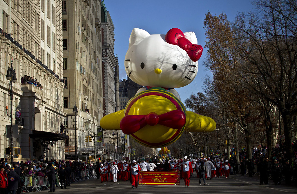 . Spectators watch as the Hello Kitty balloon floats above the street during the Macy\'s Thanksgiving Day Parade on November 28, 2013 in New York City. Despite earlier concerns about the wind, the balloons flew as planned for the parade. (Photo by Kena Betancur/Getty Images)