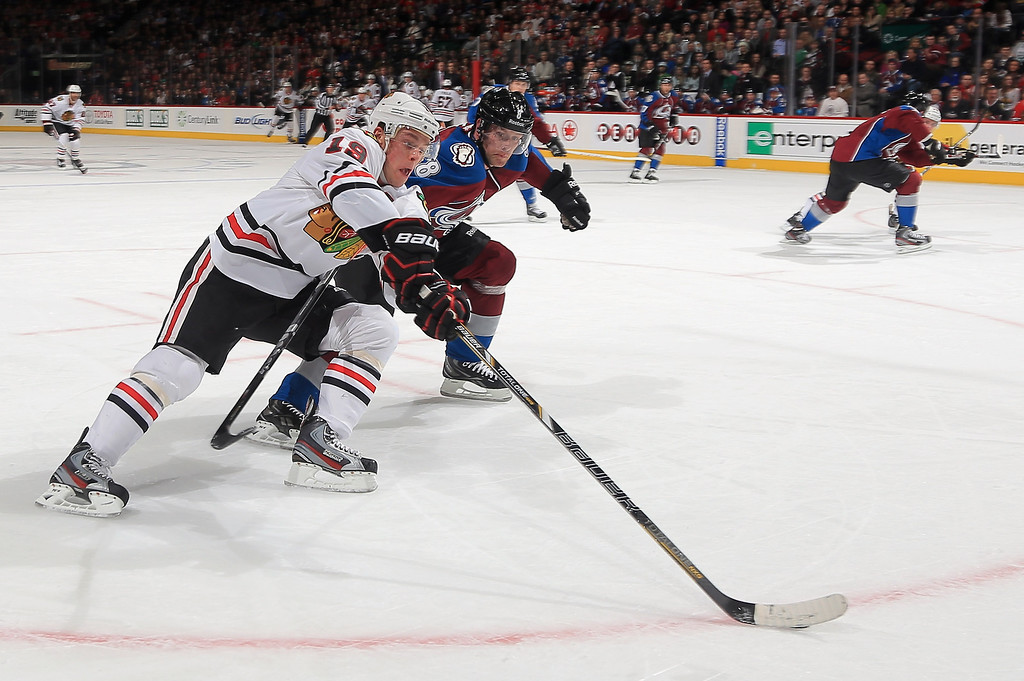 . Jonathan Toews #19 of the Chicago Blackhawks controls the puck against Jan Hejda #8 of the Colorado Avalanche at the Pepsi Center on March 18, 2013 in Denver, Colorado.  (Photo by Doug Pensinger/Getty Images)