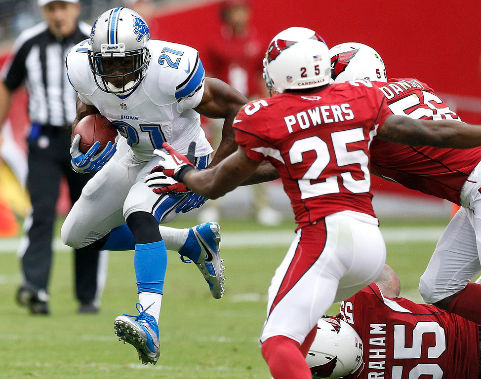 . Detroit Lions running back Reggie Bush (21) gains yards as Arizona Cardinals inside linebacker Karlos Dansby (56) John Abraham (55) and Jerraud Powers (25) defend during the first half of a NFL football game, Sunday, Sept. 15, 2013, in Glendale, Ariz. (AP Photo/Darryl Webb)