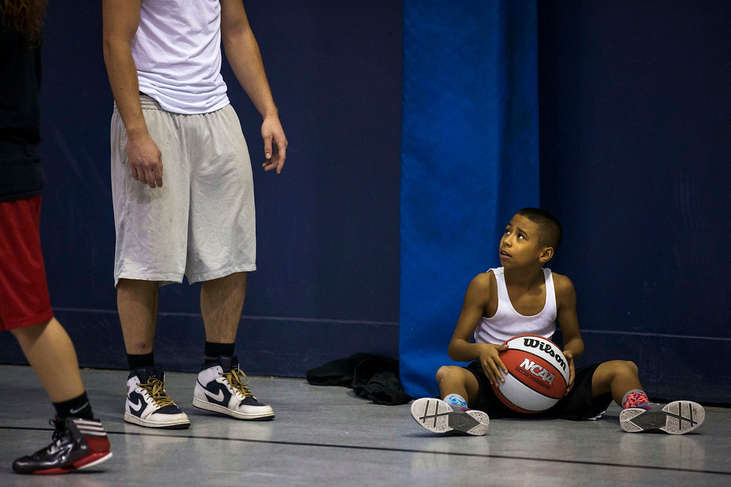 . Downey Christian high school varsity basketball player 11-year-old Julian Newman takes a break during Friday evening pickup basketball games at Downey Christian School in Orlando, Florida February 22, 2013. At 4 feet 5 inches tall, starting point guard Julian Newman stands waist high next to other players on his Florida high school basketball team. But his talent towers over the competition. At only 11, Newman leads the state of Florida in assists per game this season and ranks fifth nationally, according to Maxpreps.com, which maintains statistics on high school sports.  REUTERS/Scott Audette