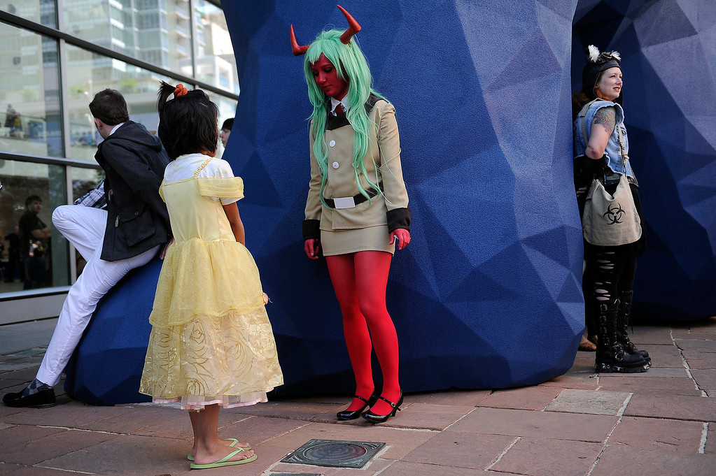 . DENVER, CO - JUNE 1: Emma Kaufman, 17, of Centennial, Colorado, center, dressed as the Anime character Scanty, answers a question from Jasmine Reeves, 8, dressed as Belle from Beauty and the Beast outside of the Colorado Convention Center during Denver Comic Con on June 1, 2013 in Denver, Colorado. (Photo by Seth McConnell/The Denver Post)