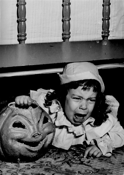 ". 1950: Becky Amato, 3, of San Jose, ""hiding under her parents\' bed,\"" demonstrates either real or feigned terror in a set-up Halloween photograph. That creepy jack-o-lantern would give us waking nightmares. (San Jose Mercury)"