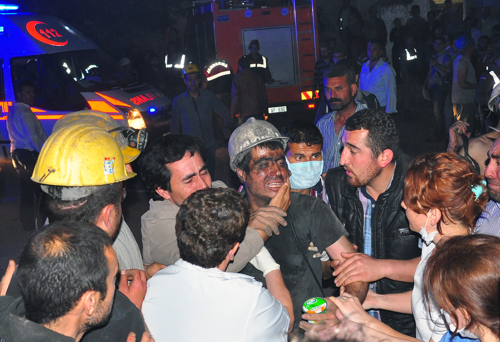 . Miners escort a rescued friend after an explosion and fire at a coal mine in Soma, in western Turkey, Tuesday, May 13, 2014. (AP Photo/IHA)