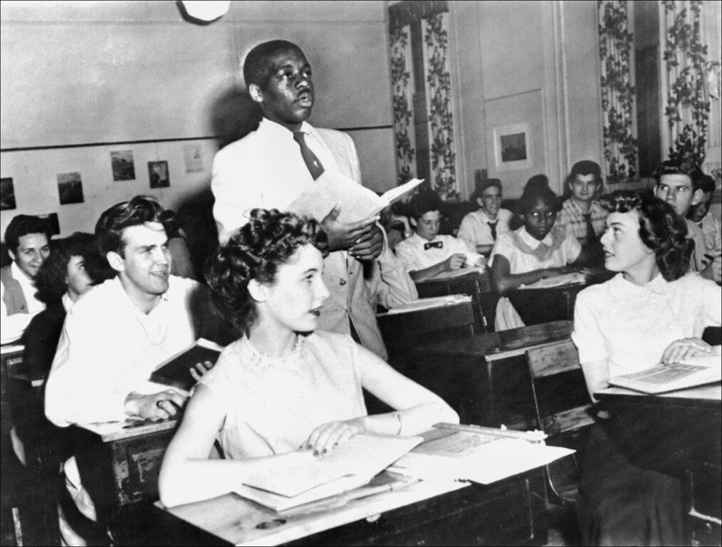 . WASHINGTON, DC - MAY 21:  A black student, Nathaniel Steward, 17, recites his lesson surrounded by white fellows and others black students, 21 May 1954 at the Saint-Dominique school, in Washington, where for the first time in USA the Brown v Board of Education decision which outlaws segregation in state schools is applied.  (Photo credit should read STAFF/AFP/Getty Images)