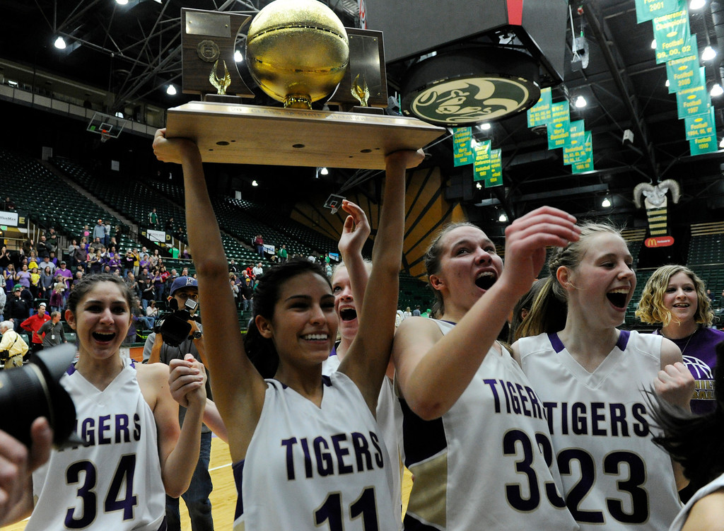 . FT. COLLINS, CO. - MARCH 16TH: Lindsey Chavez, Holy Family Tigers, hoists the 3A Colorado State Basketball Championship trophy in celebration with her teammates, Jalyn Hall, left, Claudia Pena, third from left, and Megan McGillin  after they defeated the St. Mary\'s Pirates in double overtime 53-48 at Moby Arena Saturday evening, March 16th, 2013. (Photo By Andy Cross/The Denver Post)