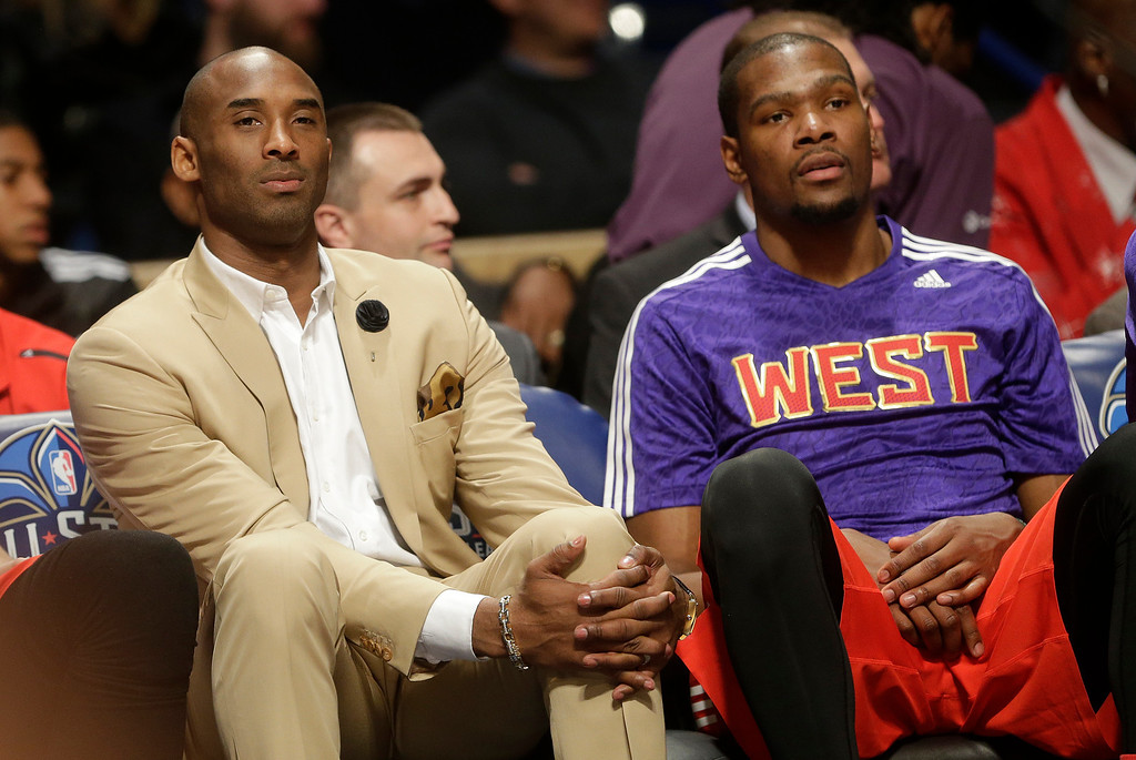 . Los Angeles Lakers Kobe Bryant, left, sits with West Team\'s Kevin Durant, of the Oklahoma City Thunder during the NBA All Star basketball game, Sunday, Feb. 16, 2014, in New Orleans. (AP Photo/Gerald Herbert)