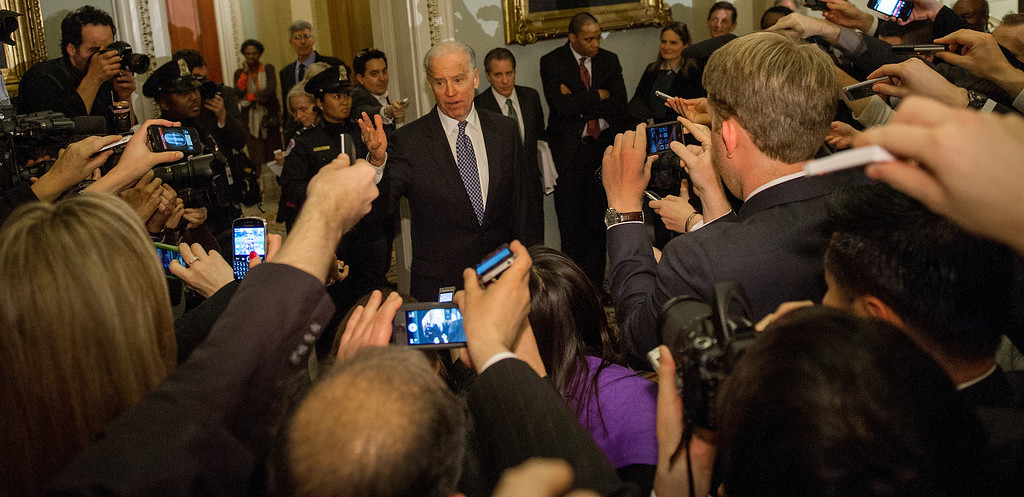 ". US Vice President Joe Biden talks with reporters in the halls of the US Senate late December 31, 2012 in Washington, DC after attending a Democrat Caucus on solving the impending fiscal cliff.  The White House and top Republicans struck a deal late December 31, 2012 to avert huge New Year tax hikes and spending cuts known as the ""fiscal cliff\"" that had threatened to send the US economy into recession.     PAUL J. RICHARDS/AFP/Getty Images"