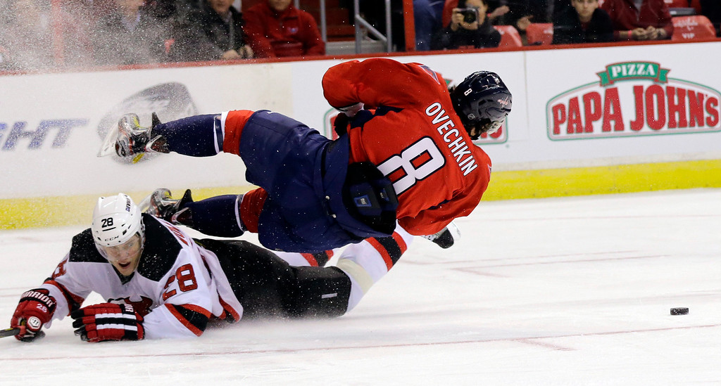 . Washington Capitals left wing Alex Ovechkin (8), of Russia, loses the puck as he falls over New Jersey Devils defenseman Anton Volchenkov (28), also of Russia, in the second period of an NHL hockey game, Thursday, Feb. 21, 2013 in Washington. The Devils won 3-2. (AP Photo/Alex Brandon)