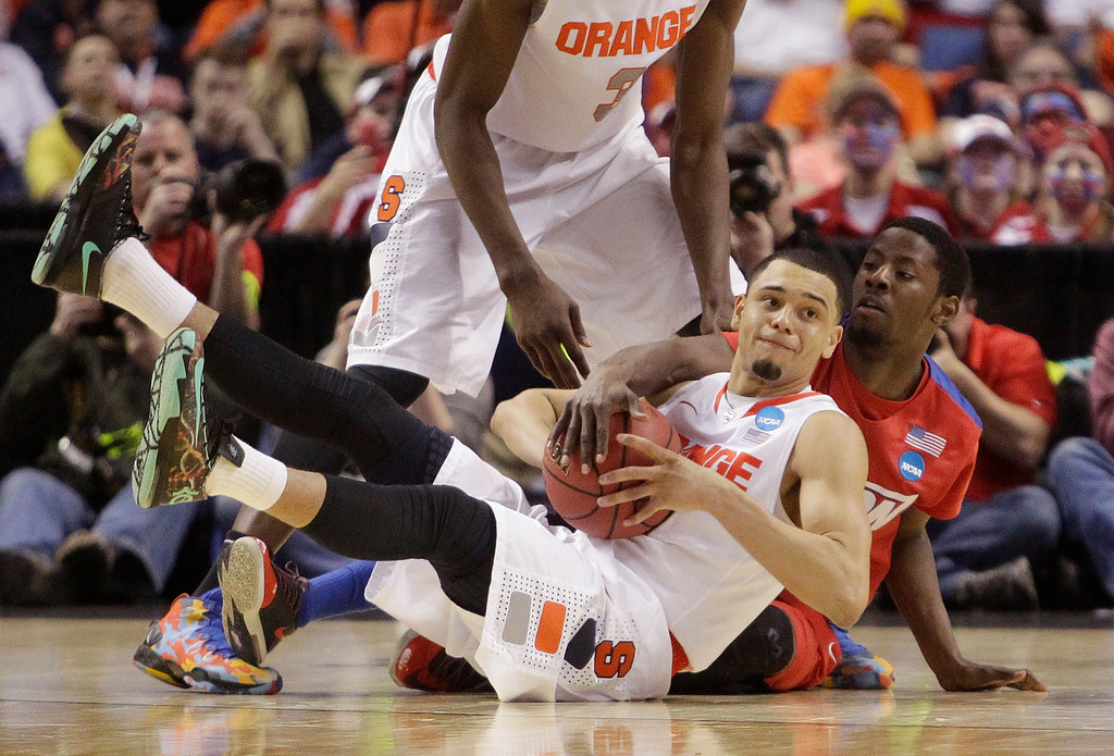 . Dayton\'s Scoochie Smith, right, and Syracuse\'s Tyler Ennis fight for control of the ball during the second half of a third-round game in the NCAA men\'s college basketball tournament in Buffalo, N.Y., Saturday, March 22, 2014. (AP Photo/Bill Wippert)