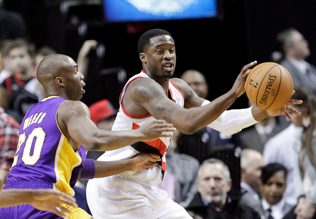. Portland Trail Blazers guard Wesley Matthews, right, passes the ball out as Los Angeles Lakers guard Jodie Meeks defends during the first half of an NBA basketball game in Portland, Ore., Monday, March 3, 2014. (AP Photo/Don Ryan)