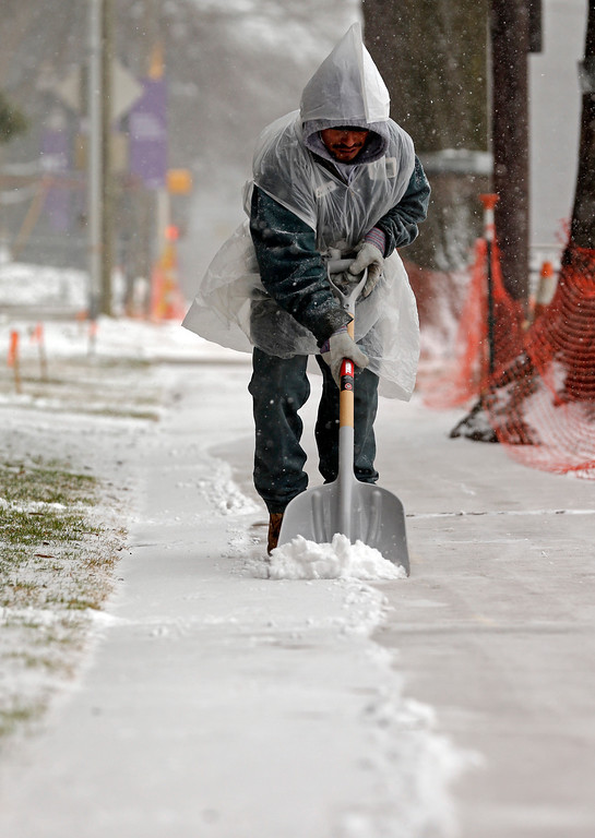 . Steven Cervantes shovels away the snow from a sidewalk as a winter storm moves into the area Wednesday, Feb. 12, 2014, in Charlotte, N.C. (AP Photo/Chuck Burton)