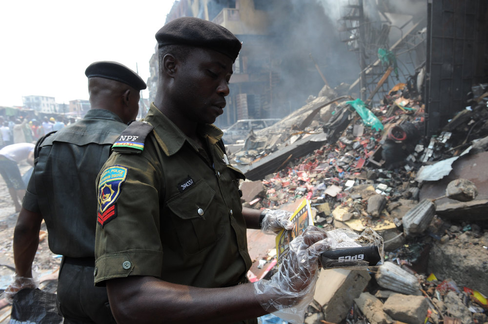 Description of . Anti-bomb policemen collect debris for examination at the scene of an explosion in a building in Lagos on December 26, 2012. Fire ripped through a crowded neighborhood in Nigeria\'s largest city and wounded at least 30 people after a huge explosion rocked a building believed to be storing fireworks, officials said.  AFP PHOTO/PIUS UTOMI EKPEI/AFP/Getty Images