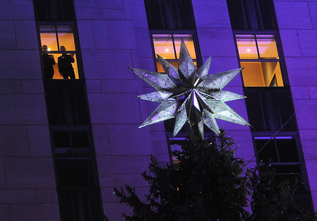 . People at the star of the Rockefeller Center Christmas tree as it is lit  during the 83rd Annual Rockefeller Center Christmas Tree Lighting Ceremony on Wednesday, Dec. 2, 2015, in New York. The Norway Spruce tree stands at about 78 feet tall and is lit with multi-colored LED lights. (Photo by Brad Barket/Invision/AP)